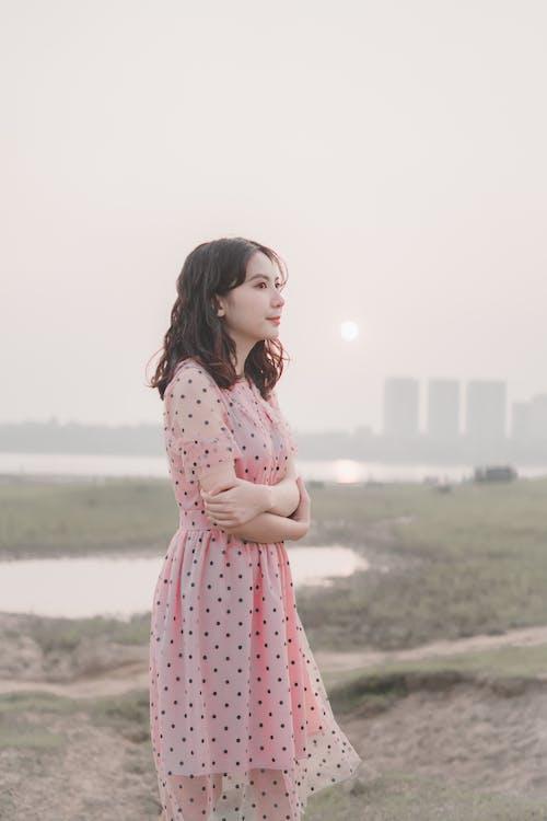 Girl in Pink Polka Dot Dress Standing on Field