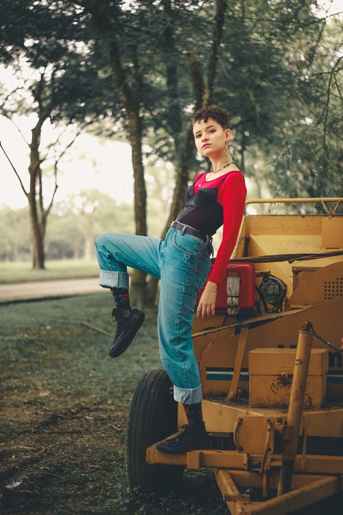 Woman in Red Top and Blue Denim Jeans Posing on Yellow Tractor