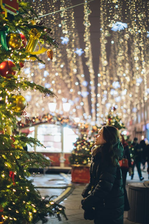 Woman in Black Coat Standing Beside Green Christmas Tree With String Lights