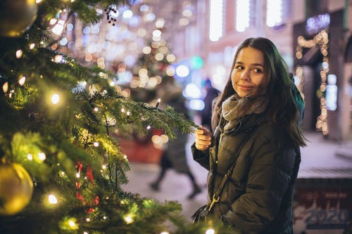 Woman in Bubble Jacket Standing Near Christmas Tree With String Lights