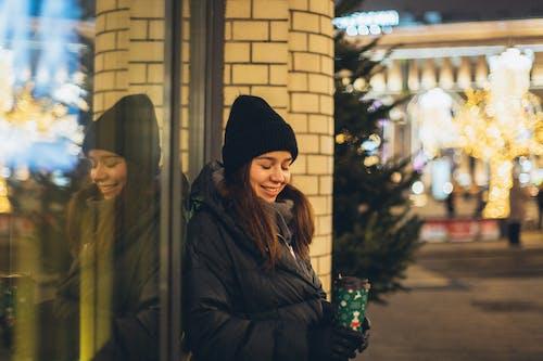 Woman in Black Knit Cap and Black Jacket Standing Near Glass Window