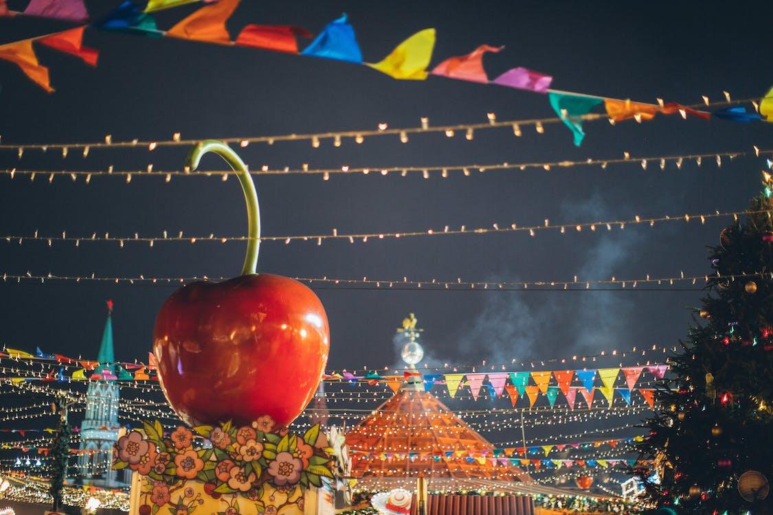 Гигантское декоративное яблоко на крыше киоска на красочной новогодней ярмарке в центре города ночью