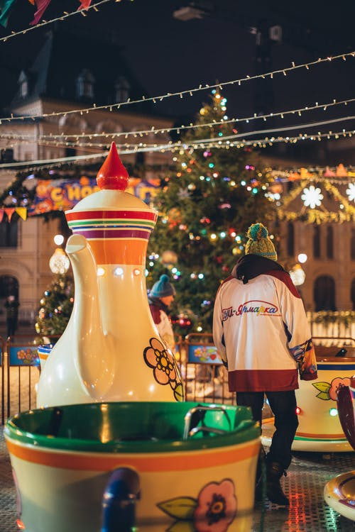 Employee servicing carousel walking among giant teapot and cups in evening park decorated in Christmas style