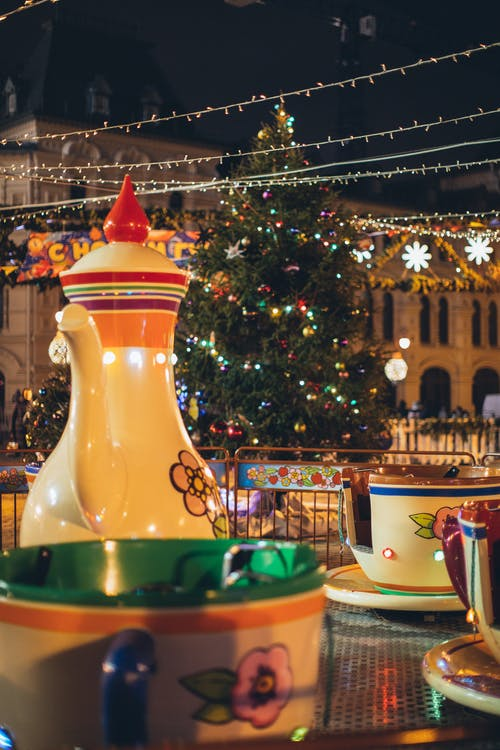 Merry go round with large colorful traditional Russian teapot and cups in city park decorated in New Year style in evening