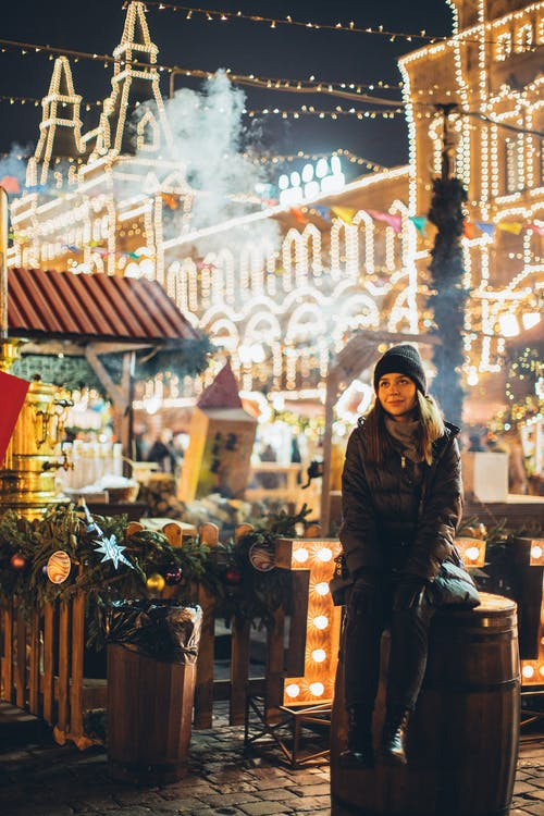 Dreamy woman in warm wear on square at New Year night