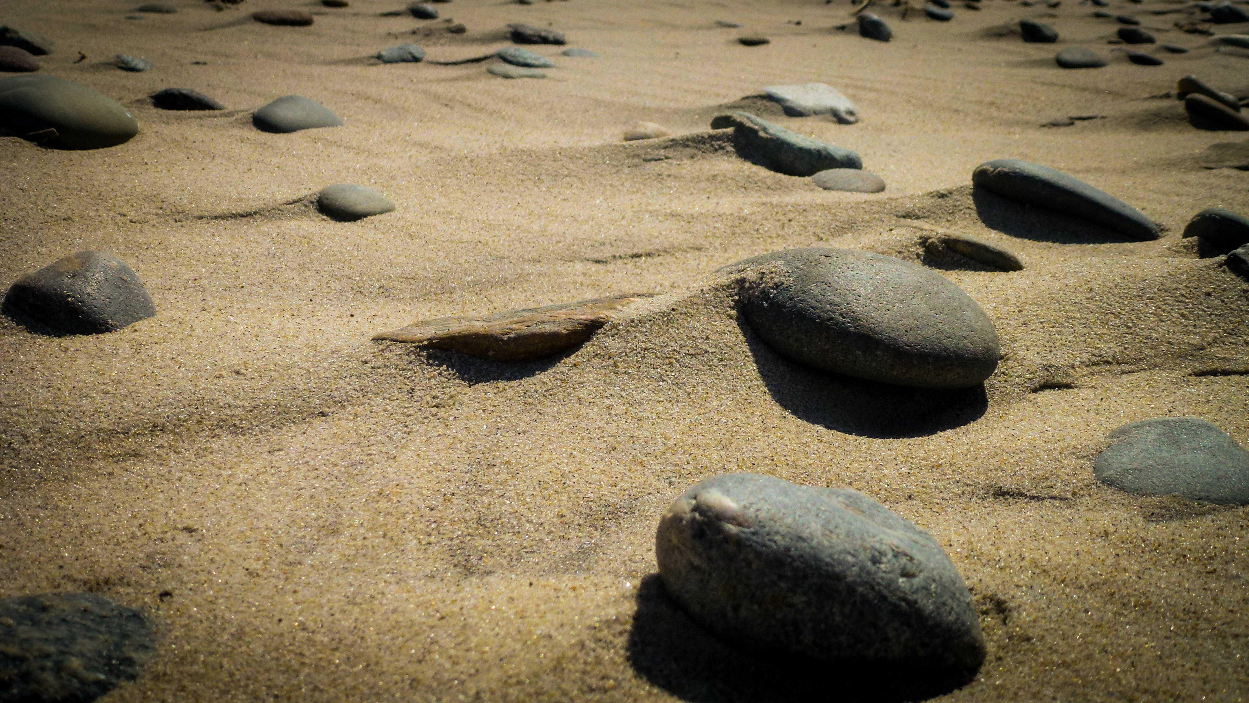 Closeup Photography of Assorted Stones on Brown Sand