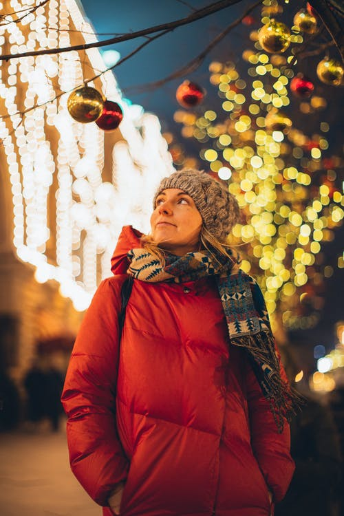 Smiling woman in city decorated for Christmas
