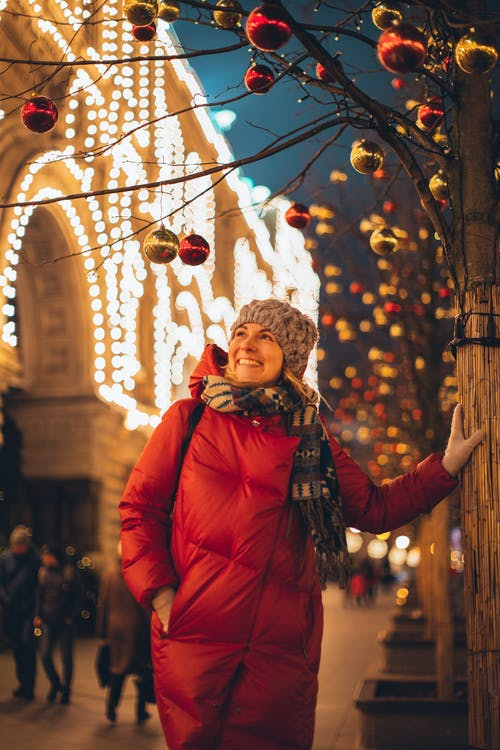 Woman in Red Bubble Jacket Standing Under Christmas Balls