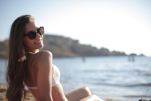 Woman in White Bikini Wearing Black Sunglasses Sitting on Rock Near Sea