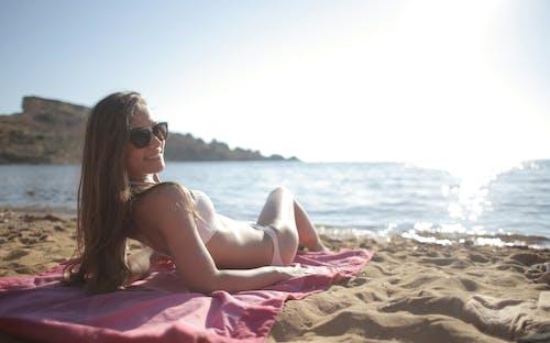Woman in White Bikini Lying on Pink Textile on Beach
