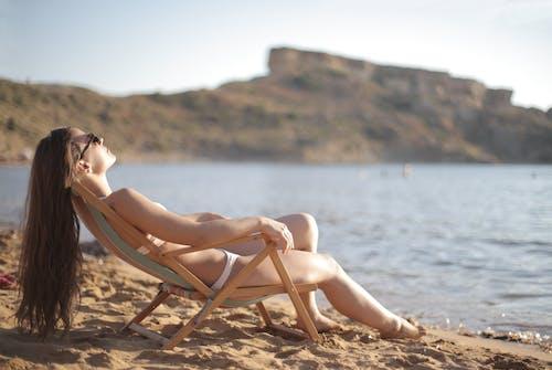Woman in White Bikini Sitting on Brown Wooden Folding Chair Near Body of Water