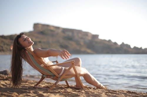 Woman in Bikini Sitting on Brown Wooden Folding Chair