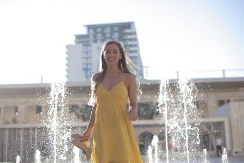 Woman in Yellow Spaghetti Strap Dress Standing on Water Fountain