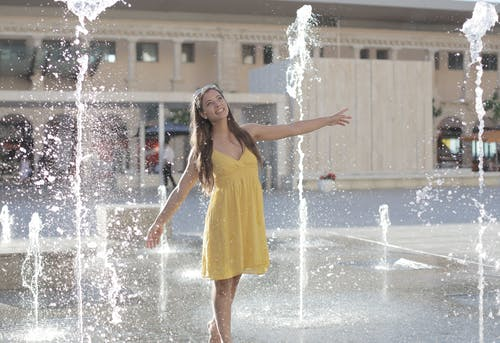 Woman in Yellow Sleeveless Dress Standing on Water Fountain