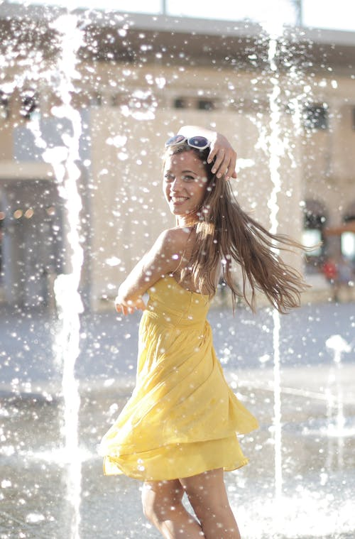 Woman in Yellow Dress Standing Near Water Fountain While Smiling