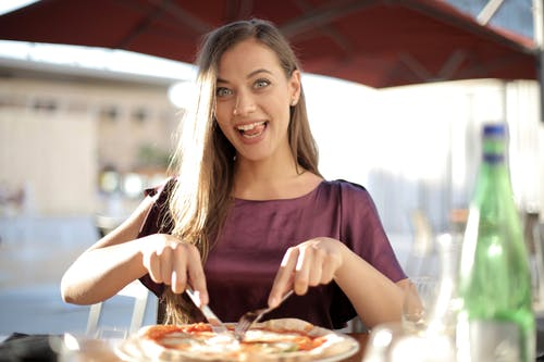 Photo of Woman in Purple Top While Slicing Pizza