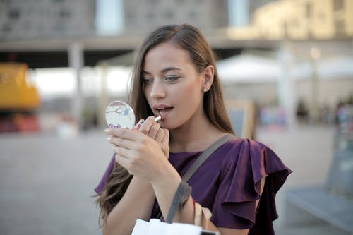 Shallow Focus Photo of Woman Applying Lipstick