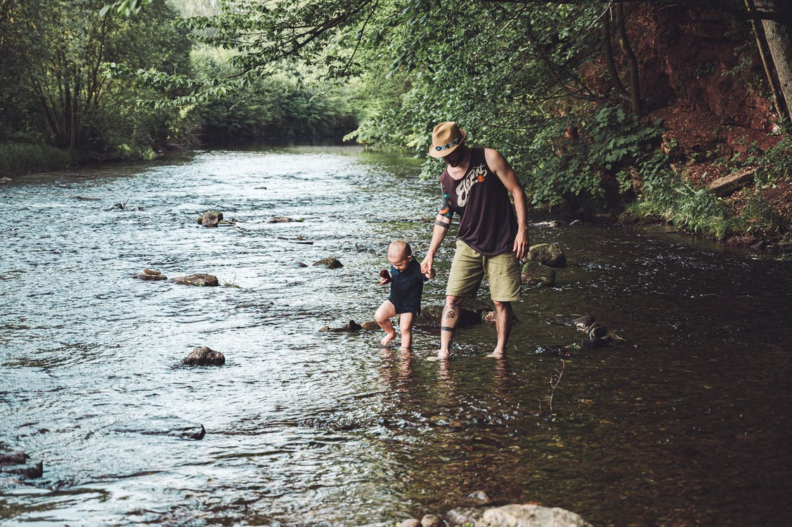 Photo of Man Holding His Child While Walking in the River