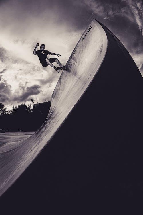 Monochrome Photo of Man Skateboarding on Skate Ramp