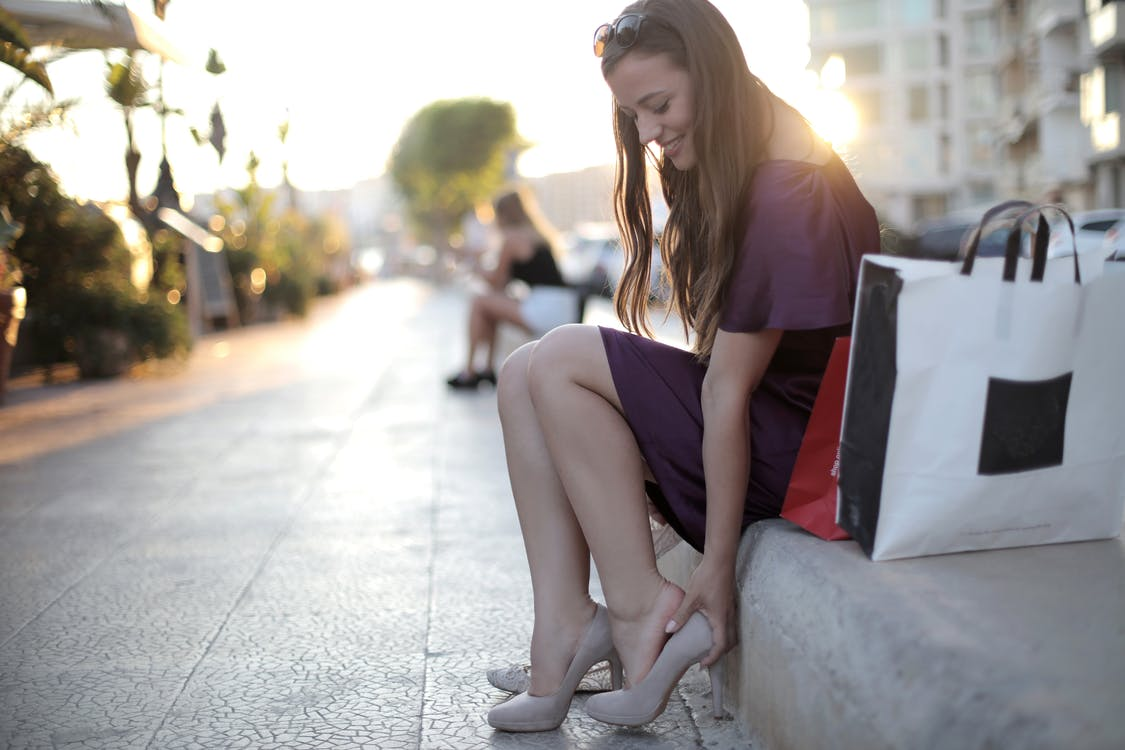 Shallow Focus Photo of Woman Sitting on Concrete Bench While Fitting Her High Heels