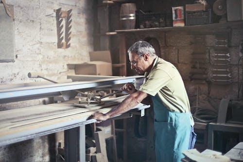 Photo of Man Using Gray Metal Tool