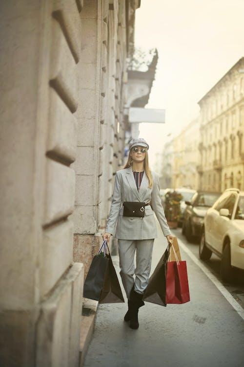 Woman in Gray Coat Walking on Sidewalk