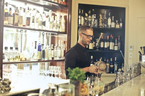 Man in Black Top Standing in Front of Bar Counter