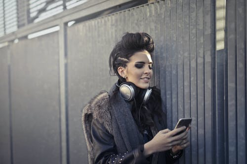 Woman in Black and Brown Fur Coat Wearing Black Headphones
