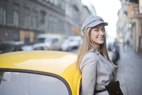Woman in Gray Hat and Gray Coat Standing Beside Yellow Car