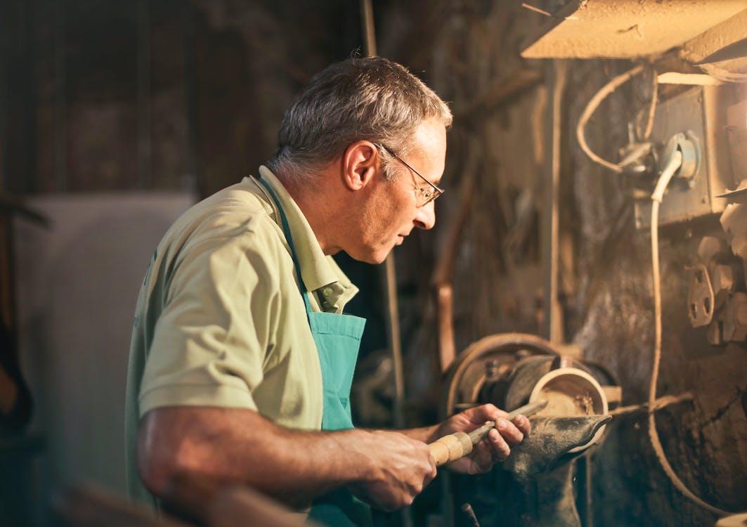 Senior male turner working on lathe machine in workshop