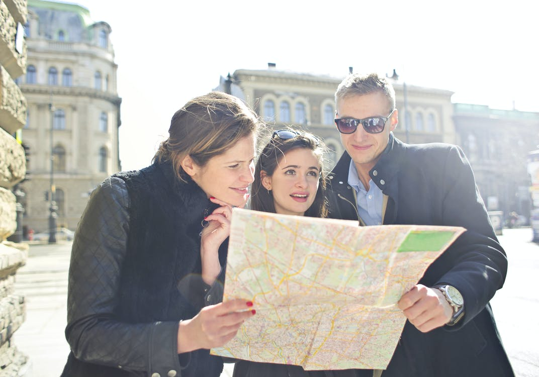 People Reading Map in the Middle of the Street