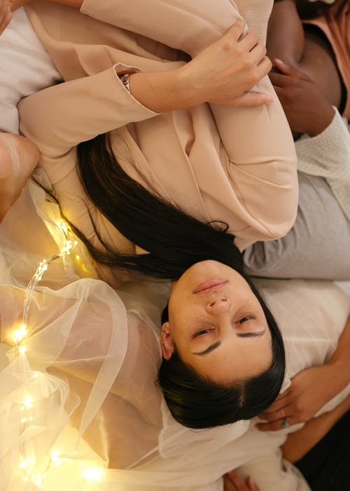 Tired ethnic woman on bed with friends after party