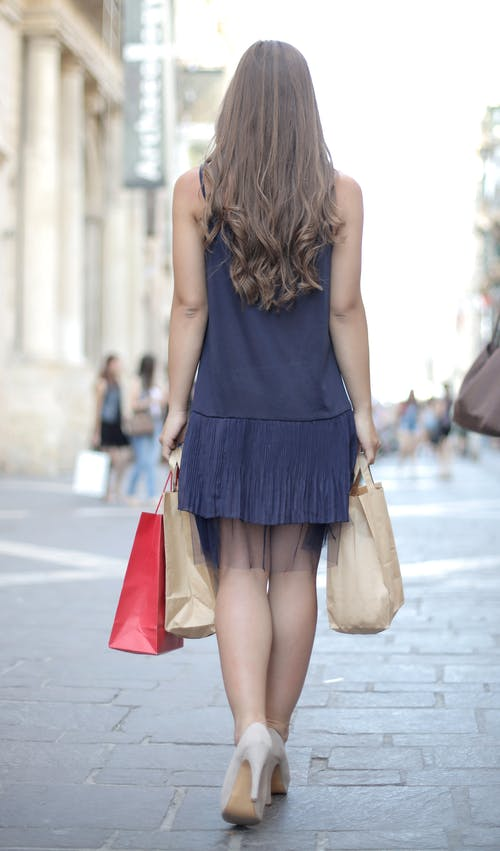 Woman in Black Sleeveless Dress Holding Brown Leather Handbag