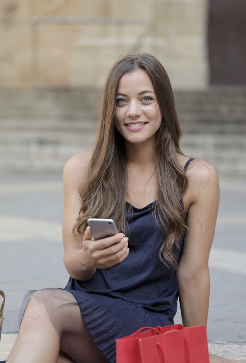 Woman in Blue Sleeveless Dress Holding Silver Iphone 6
