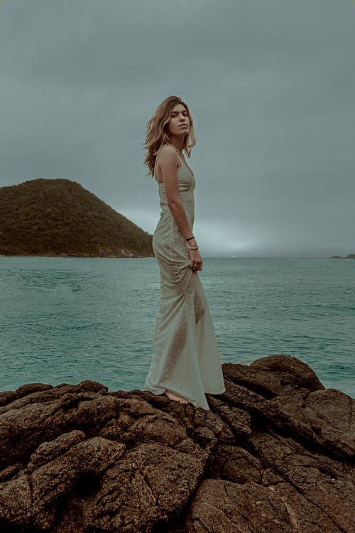 Woman in White Sleeveless Dress Standing on Brown Rock Near Body of Water