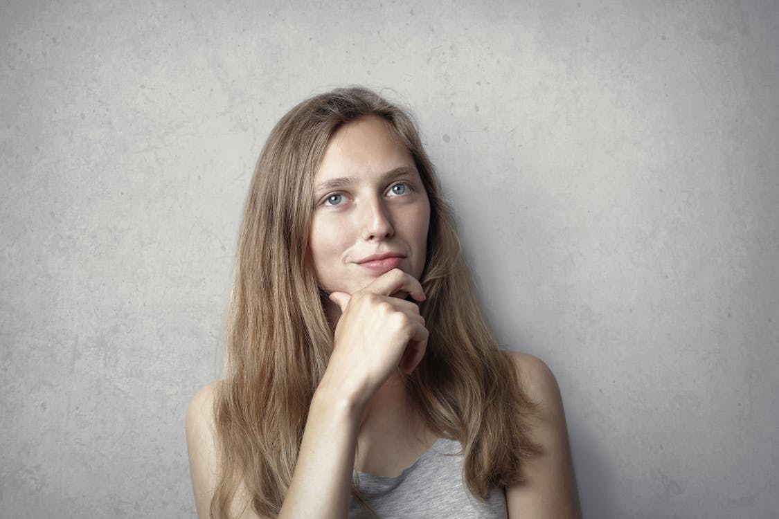 Woman in Gray Tank Top While Holding Her Chin