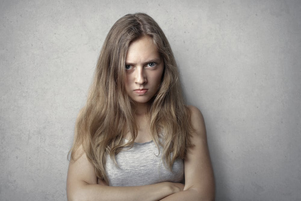 An angry woman in gray tank top. | Photo: Pexels