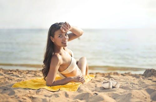 Woman in White Bikini Lying on Yellow Textile on Beach