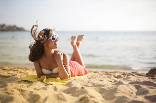 Shallow Focus Photo of Woman Lying Down on Beach While Wearing Sunglasses