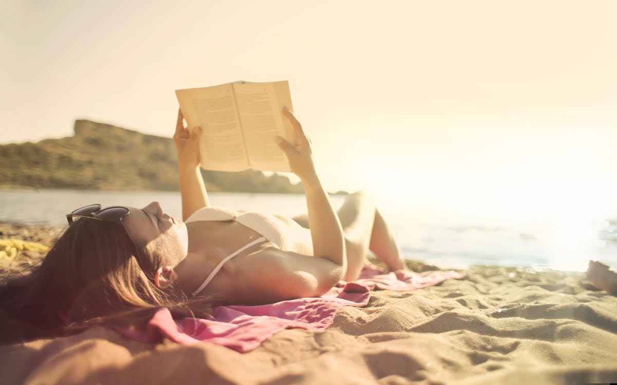 Woman Lying on Beach Reading Book
