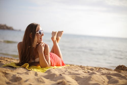 Photo of Woman Wearing Sunglasses While Lying on Beach