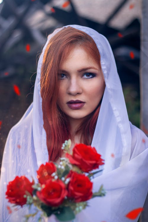 Woman in White Hijab Holding Red Rose Bouquet