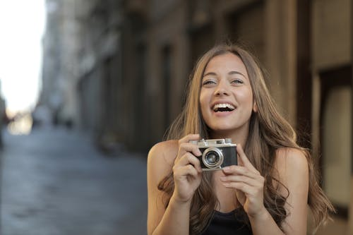 Woman in Black Tank Top Holding Silver Camera