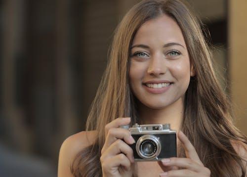 Mulher Sorridente Segurando Uma Câmera Cinza E Preta
