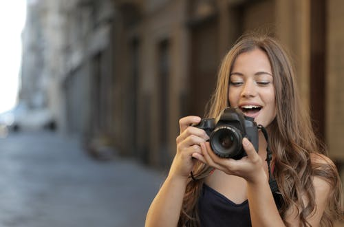 Woman in Black Tank Top Holding Black Dslr Camera