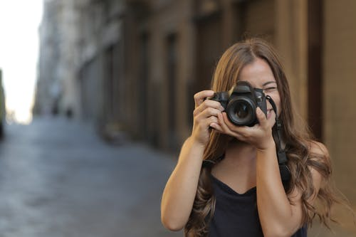 Woman in Black Tank Top Holding Black Dslr Camera