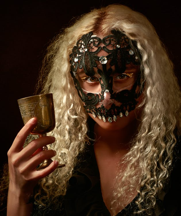 Photo of Person Wearing Masquerade Mask While Holding Goblet