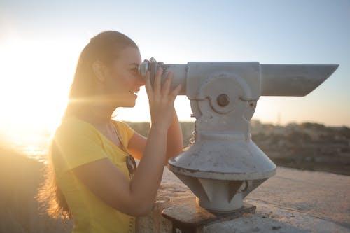 Woman in Yellow T-shirt Using Gray Binoculars