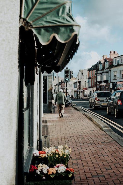 Man in Green Jacket Walking on Sidewalk