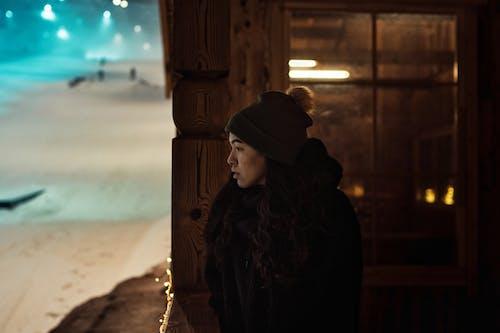 Woman in Black Hoodie Standing Near Brown Wooden Wall